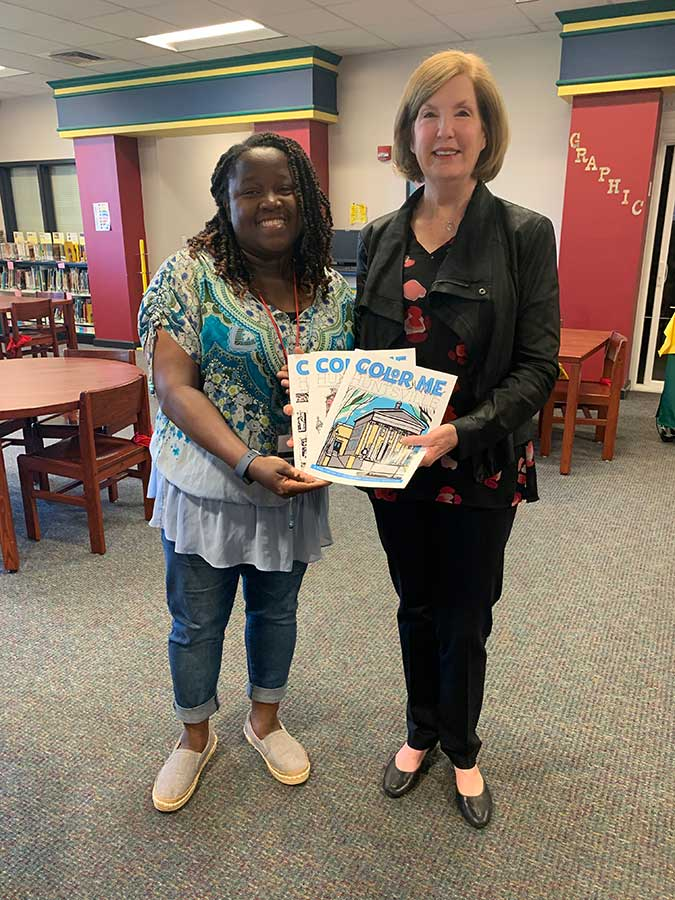 Donna presenta a set of Color Me, Huntsville coloring books to the Riverton Elementary School library.